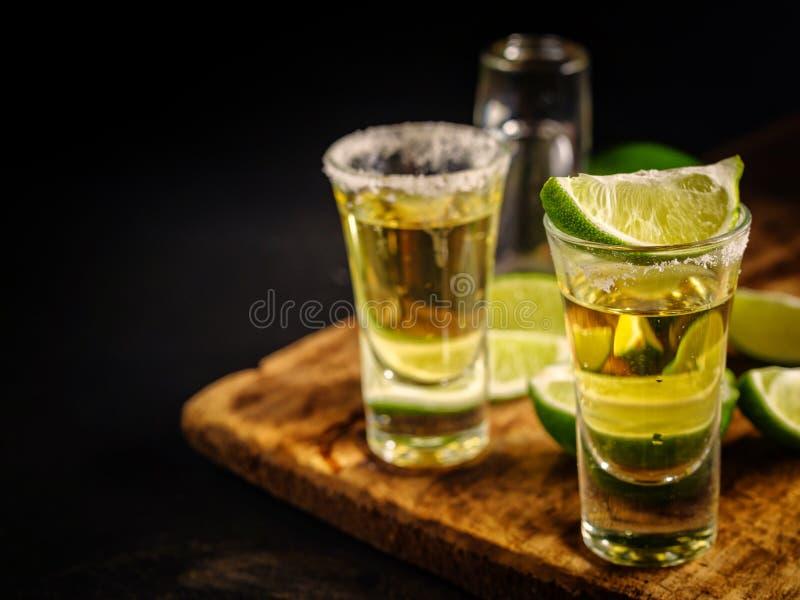 Tequila mexicano del oro con la cal y la sal en la tabla de madera fotografía de archivo libre de regalías