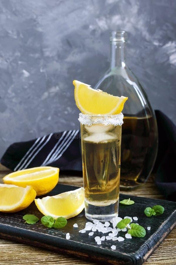 Tequila mexicano del oro en el vaso de medida con el limón y la sal del mar en la tabla oscura foto de archivo