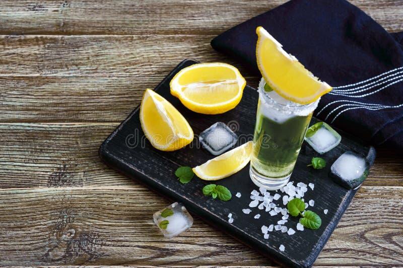 Tequila mexicano del oro en el vaso de medida con el limón y la sal del mar en la tabla oscura fotos de archivo