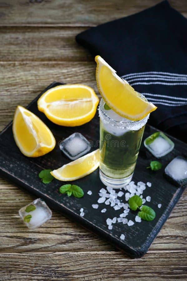 Tequila mexicano del oro en el vaso de medida con el limón y la sal del mar en la tabla oscura fotografía de archivo libre de regalías