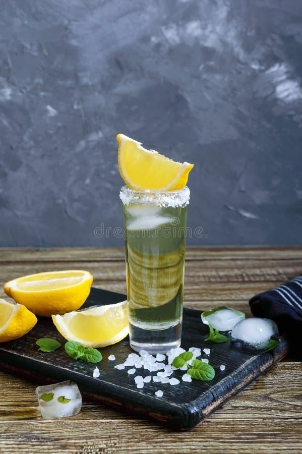 Tequila mexicano del oro en el vaso de medida con el limón y la sal del mar en la tabla oscura fotografía de archivo