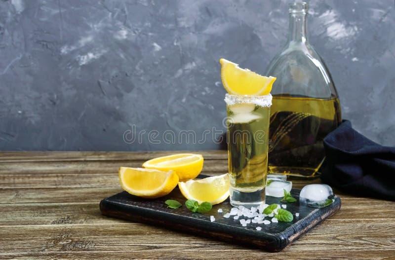 Tequila mexicano del oro en el vaso de medida con el limón y la sal del mar en la tabla oscura fotos de archivo libres de regalías