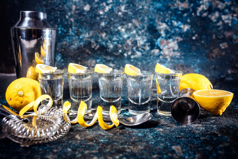 Tequila shots with lemon slices and cocktail elements. Alcoholic drinks in shot glasses served in pub or bar. Silver tequila shots with lemon slices and cocktail royalty free stock images