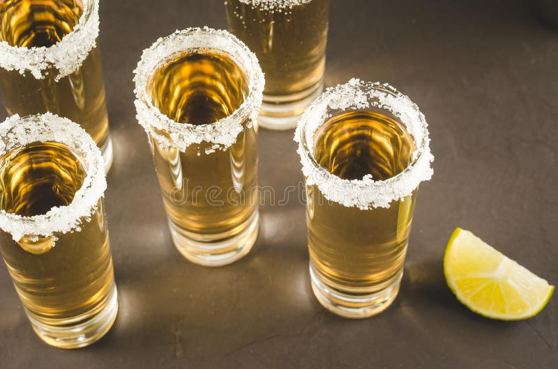 Tequila shots with lime fruit and salt/Tequila shots with lime fruit and salt on a dark background. Top view royalty free stock photos