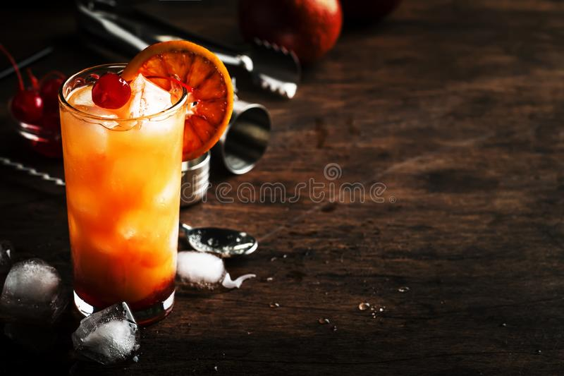 Tequila sunrise alcoholic cocktail with silver tequila, grenadine syrup, orange and ice cubes. Wooden bar counter background. Summer mood concept. Selective royalty free stock photography