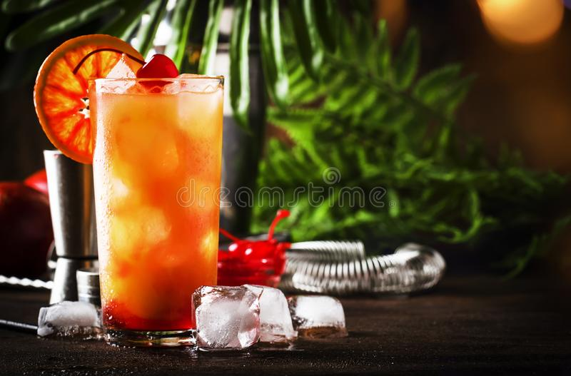 Tequila sunrise alcoholic cocktail with silver tequila, grenadine syrup, orange and ice cubes. Wooden bar counter background. Summer mood concept. Selective stock photo