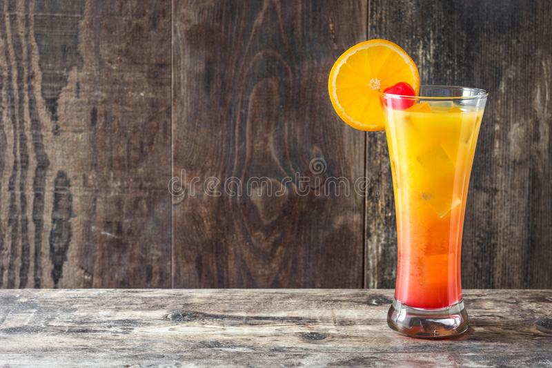Tequila sunrise cocktail in glass on wood royalty free stock images