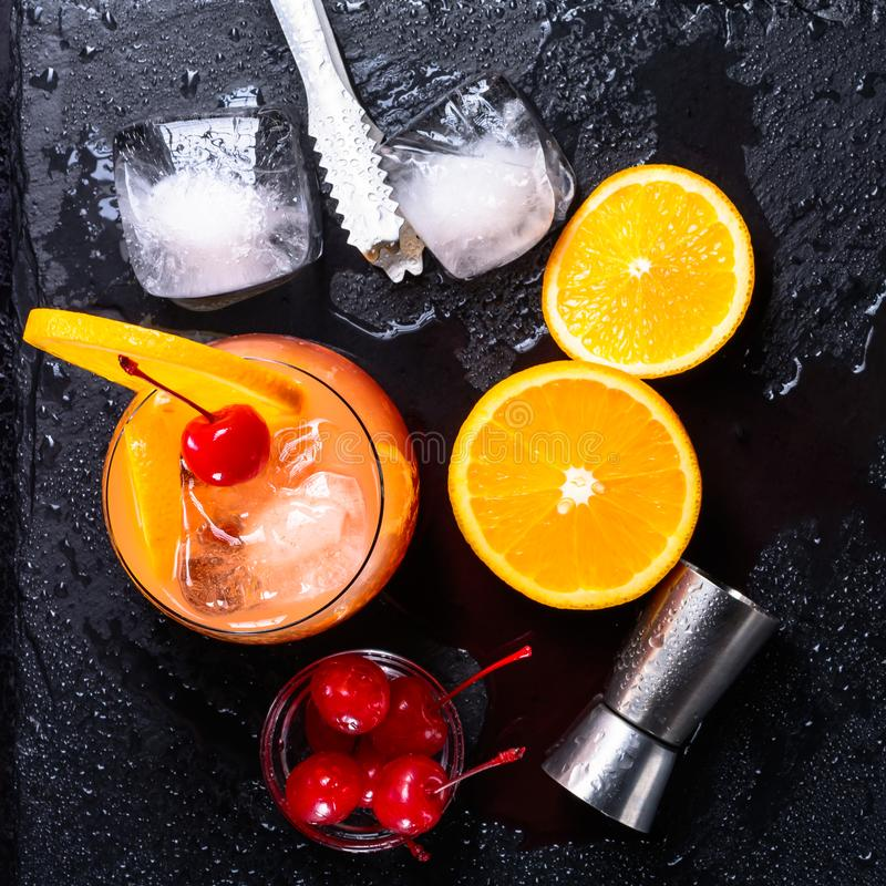 Tequila Sunrise cocktail, orange, ice cubes, maraschino cherries, ice tongs and jigger on a wet black slate tray. Cocktail Set. To royalty free stock photos