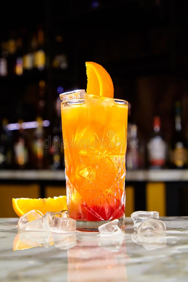 Tequila Sunrise cocktail or similar, for example Jagermonstr  with tequila, grenadine and orange juice. On the bar stock photography