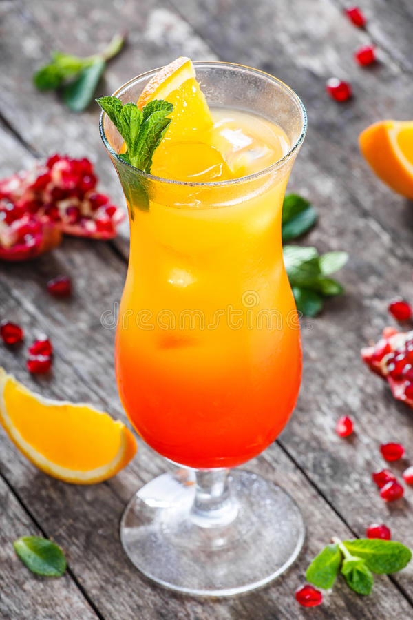 Free Tequila Sunrise Cocktail With Mint, Orange And Pomegranate In Tall Glass On Wooden Background. Summer Drinks And Alcoholic Cocktai Royalty Free Stock Photography - 93248237
