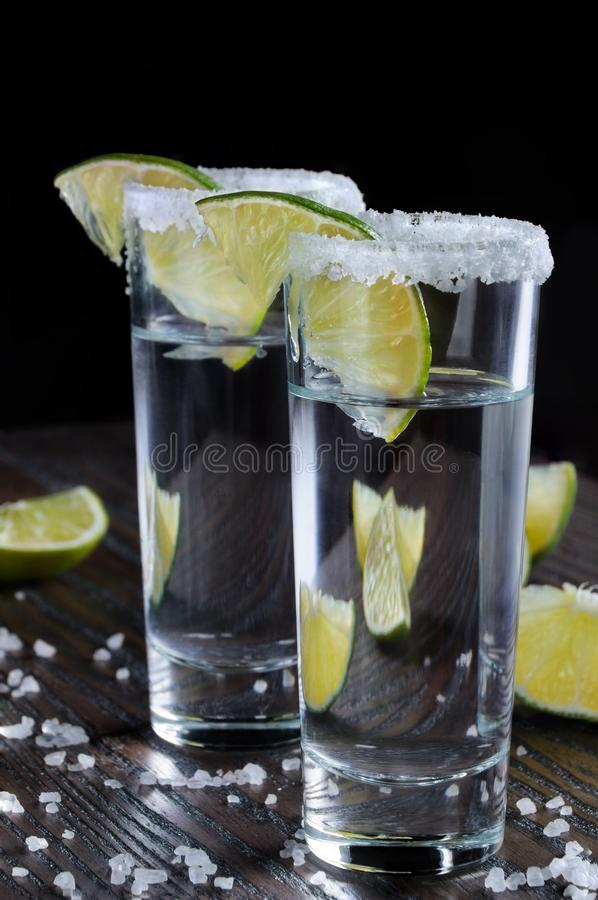 Tequila tall shot glasses with lime. Portion of tequila, framed with a salt edge with slice lime in tall shot glasses royalty free stock image