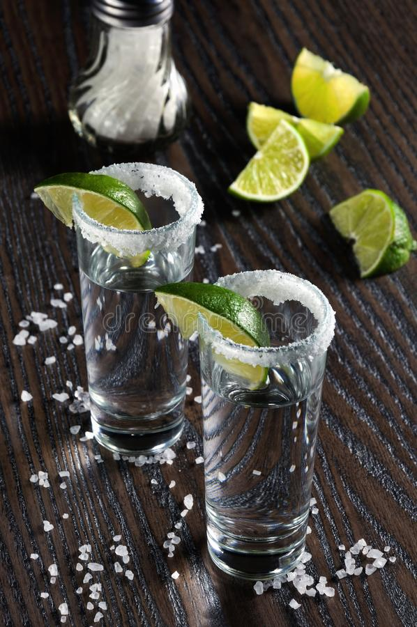 Tequila tall shot glasses with lime. Portion of tequila, framed with a salt edge with slice lime in tall shot glasses stock photography