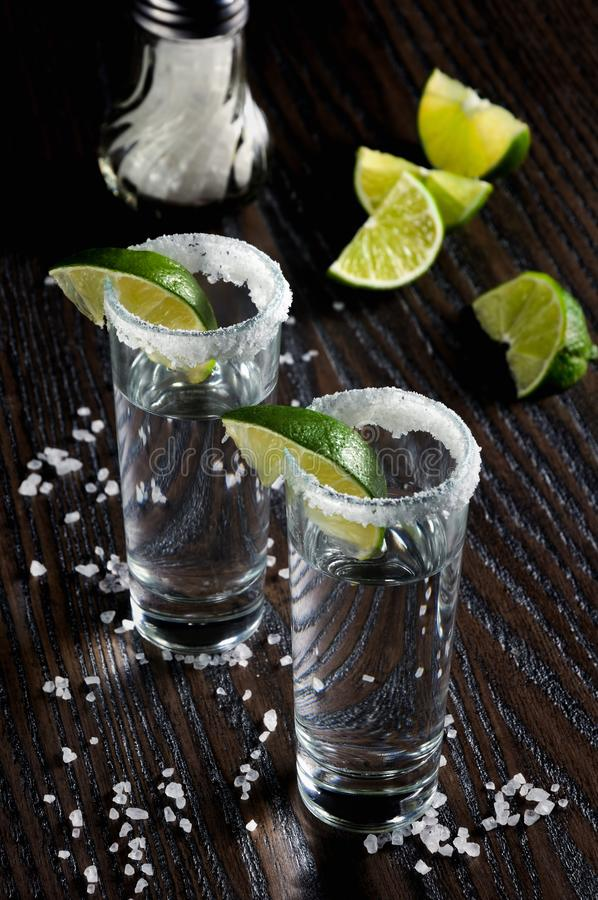 Tequila tall shot glasses with lime. Portion of tequila, framed with a salt edge with slice lime in tall shot glasses stock photos