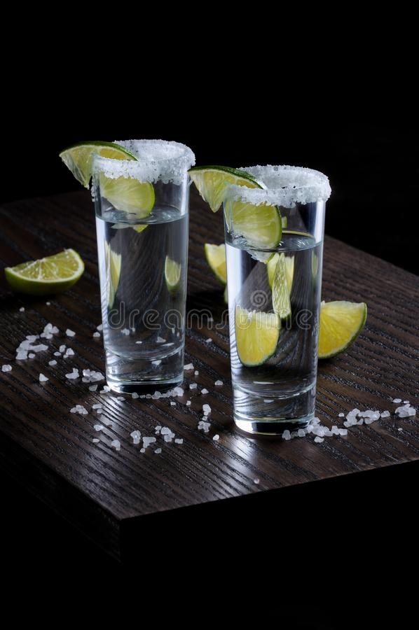 Tequila tall shot glasses with lime. Portion of tequila, framed with a salt edge with slice lime in tall shot glasses stock image