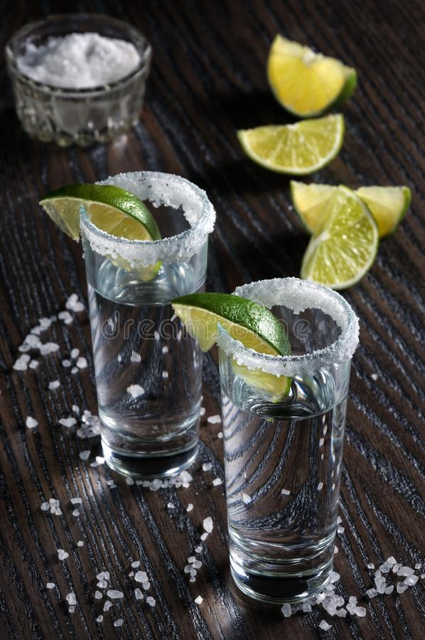 Tequila tall shot glasses with lime. Portion of tequila, framed with a salt edge with slice lime in tall shot glasses royalty free stock images