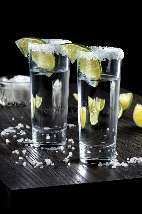 Tequila tall shot glasses with lime. Portion of tequila, framed with a salt edge with slice lime in tall shot glasses stock photo