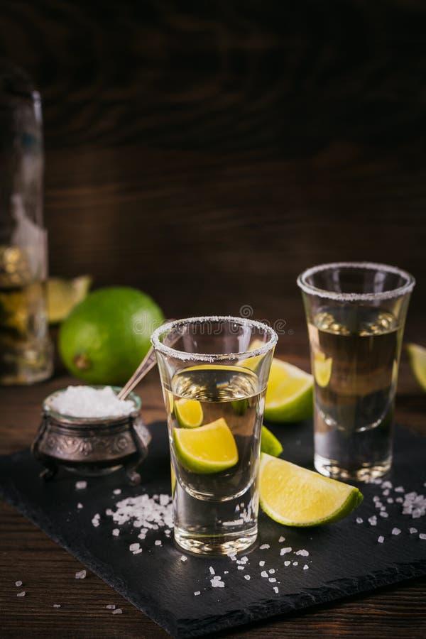 Tequila tirado con la cal y la sal del mar fotografía de archivo