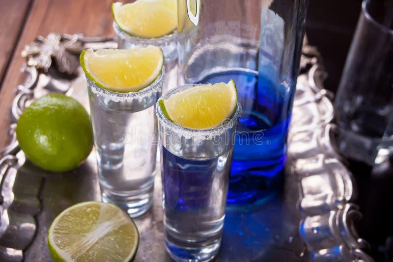 Tequila tirado con la sal de la cal y del mar y la botella azul en la bandeja foto de archivo libre de regalías
