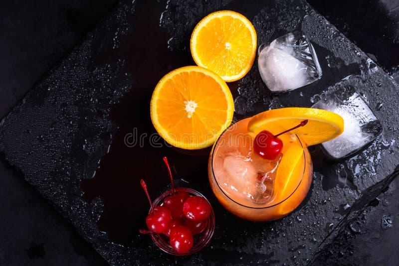Tequila wschodu słońca koktajl, pomarańcze, kostki lodu i maraskino wiśnie na mokrym czerni, krytykujemy tacę Odgórny widok z kop zdjęcia royalty free
