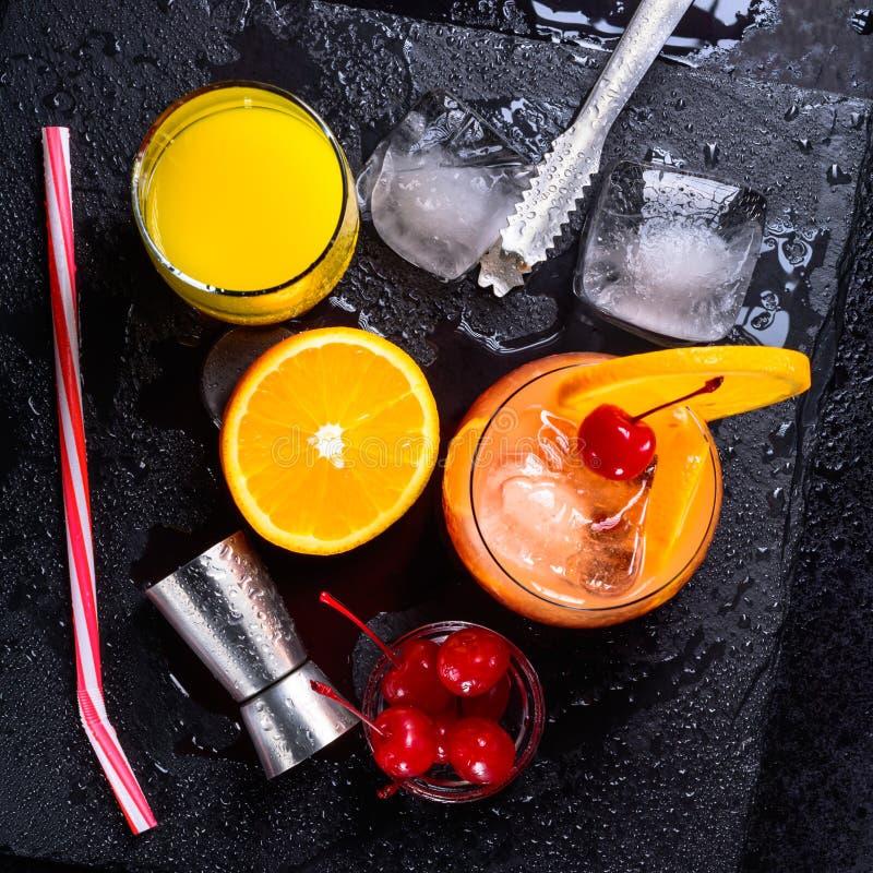 Tequila wschodu słońca koktajl, pomarańcze, kostki lodu, maraskino wiśnie, lodowi tongs, osadzarka i słoma na czarnym, moczymy łu obraz stock