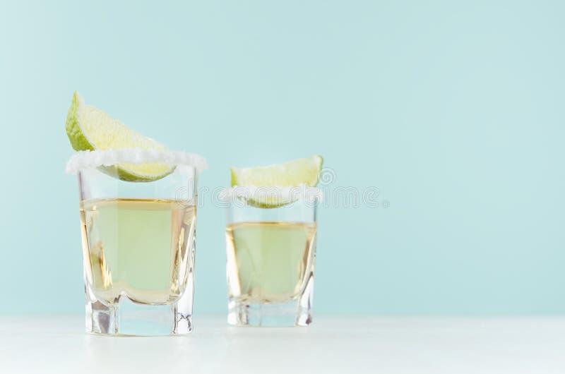 Tequilacocktail met zoute rand, stuk groene kalk in geschotene glazen op zachte lichte pastelkleur blauwe achtergrond, exemplaarr royalty-vrije stock fotografie