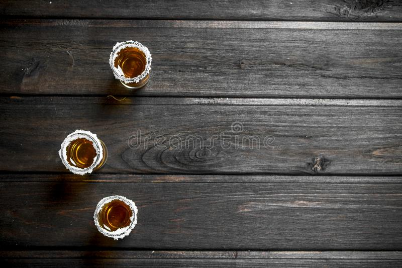 Tequilaen i ett skjutit exponeringsglas av saltar arkivfoto