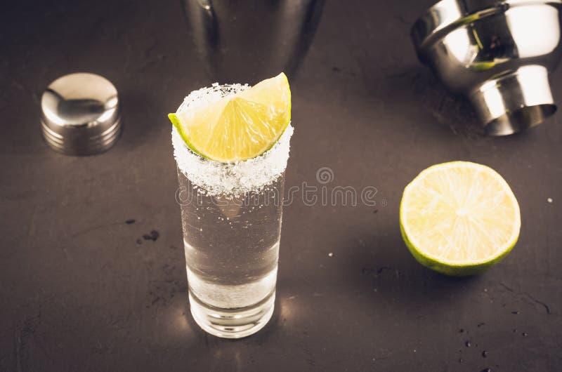 Tequilaen som sk?ts med den limefruktfrukt och shaker/Tequila, sk?t med den limefruktfrukt och shaker p? en m?rk bakgrund Selekti arkivfoton