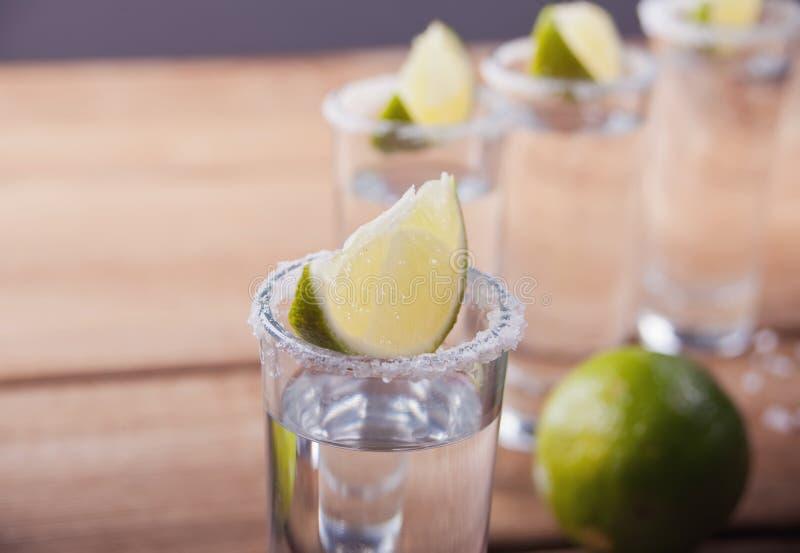 Tequilaen som skjutas med limefrukt, och havet saltar på den gamla trätabellen, selektiv fokus arkivfoton