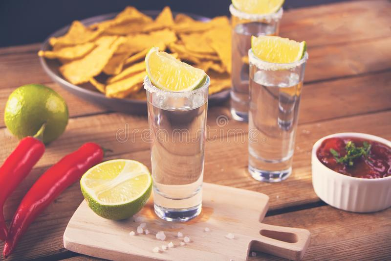 Tequilaen som skjutas med limefrukt, och havet saltar på trätabellen royaltyfria bilder