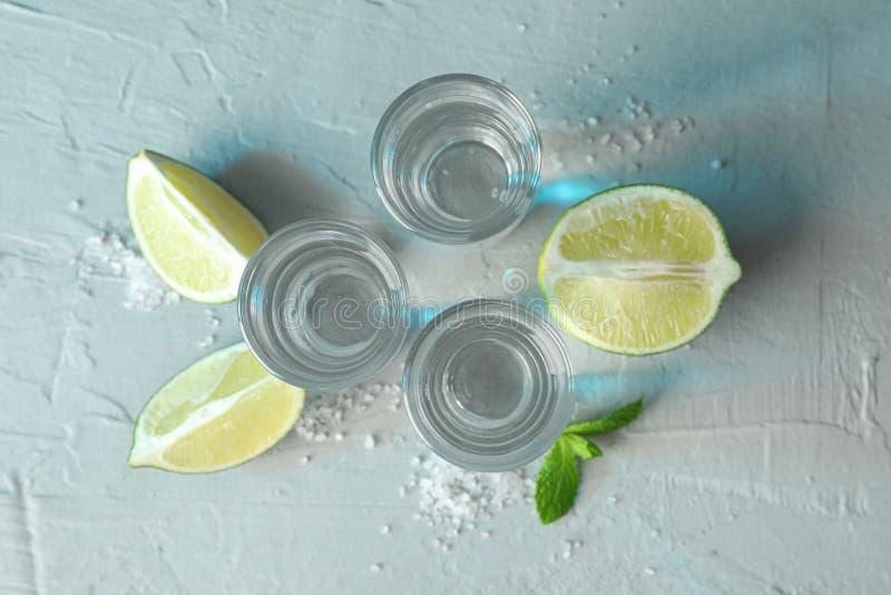 Tequilaschoten, zout, kalkplakken en munt op witte achtergrond royalty-vrije stock fotografie