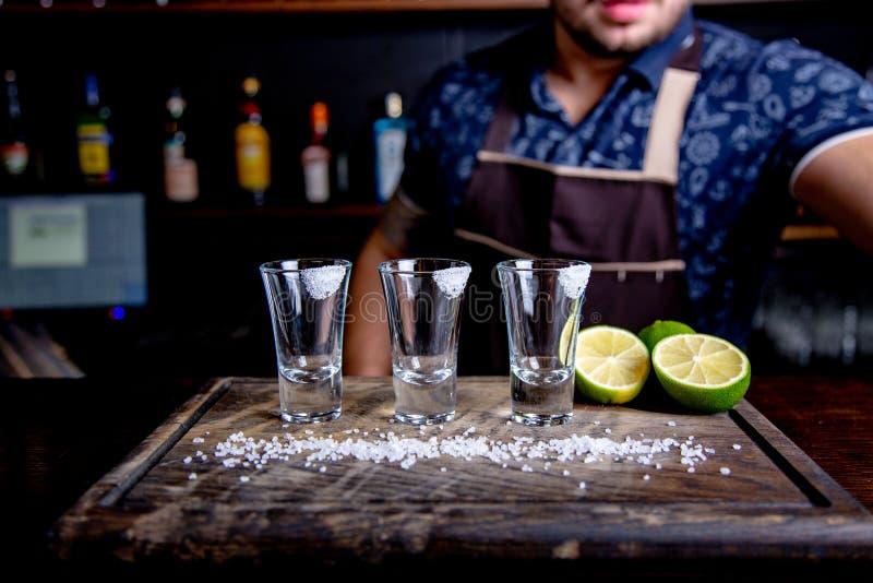 Tequilasilver, alkohol i sköt exponeringsglas, limefrukt och saltar, den tonade bilden, selektiv fokus arkivbild