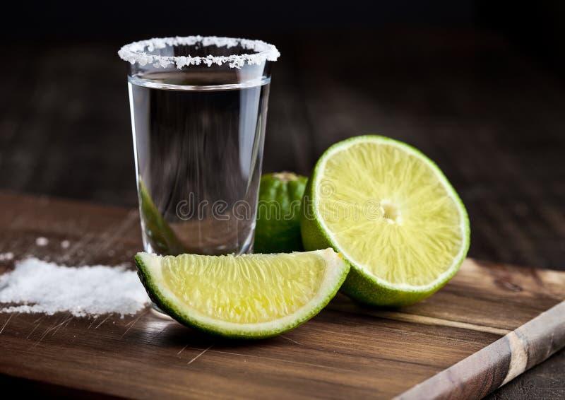 Tequilasilverskottet med limefruktskivor och saltar på träbräde arkivfoto