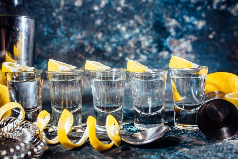 Tequilaskott med citronskivor och coctaildetaljer Alkoholdrycker i skottexponeringsglas tjänade som i bar eller stång royaltyfri foto