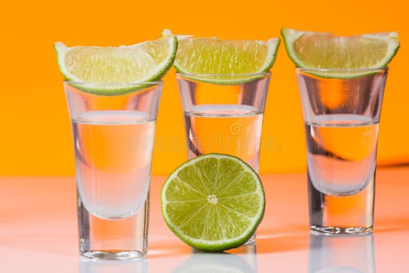 Tequilaskott med en skiva av limefrukt på den glass orange bakgrunden royaltyfri fotografi