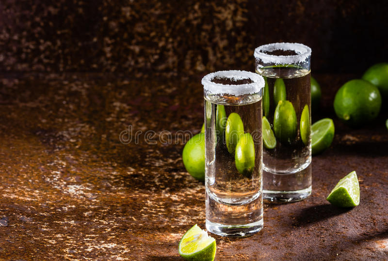 Tequilaskott med limefrukt och havet saltar, den selektiva fokusen arkivbild