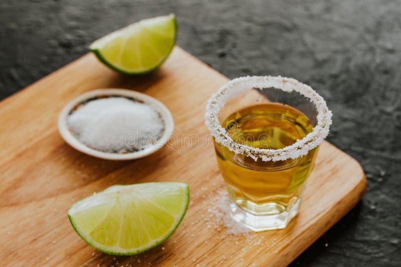 Tequilaskott, mexikanska alkoholiserade starka drinkar och stycken av limefrukt med salt i Mexiko royaltyfri bild