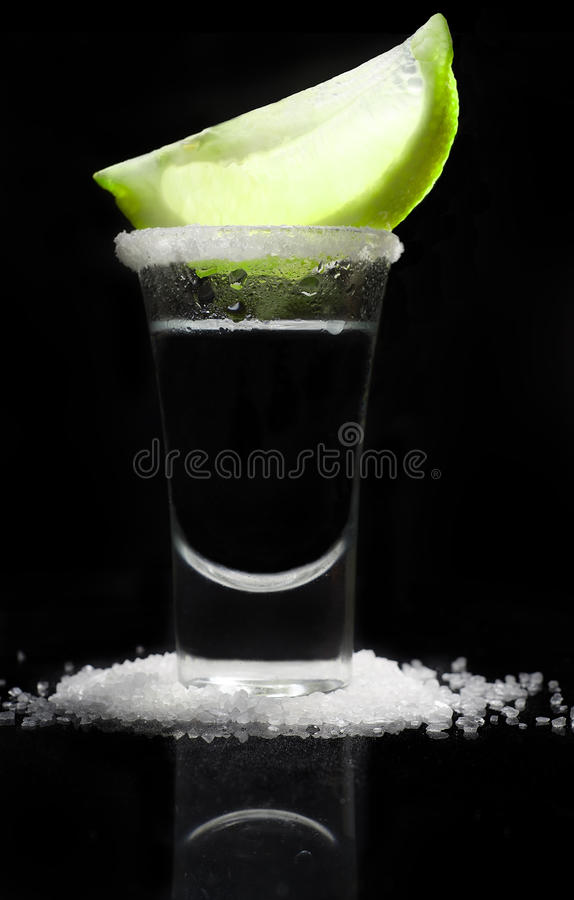 Tequilla in a glass on a reflective black background royalty free stock photography