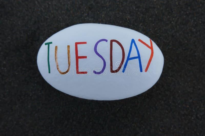 Terça-feira, segundo dia da semana cinzelada e pintada em uma pedra branca sobre a areia vulcânica preta foto de stock
