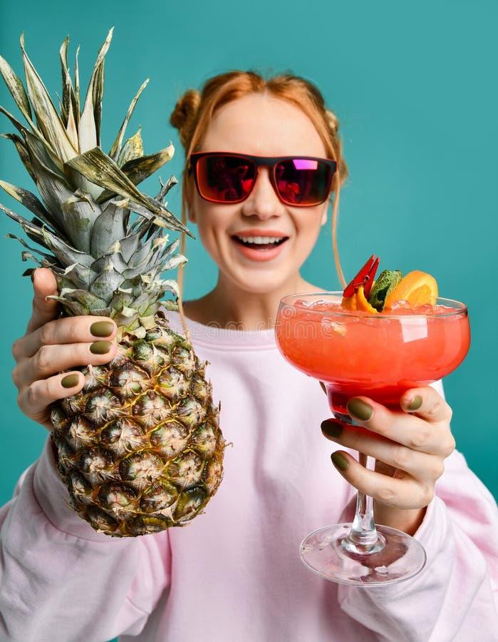 Ter a mulher amigável do divertimento em óculos de sol da forma convida para juntar-se e entrega-nos um cocktail do margarita da  fotos de stock