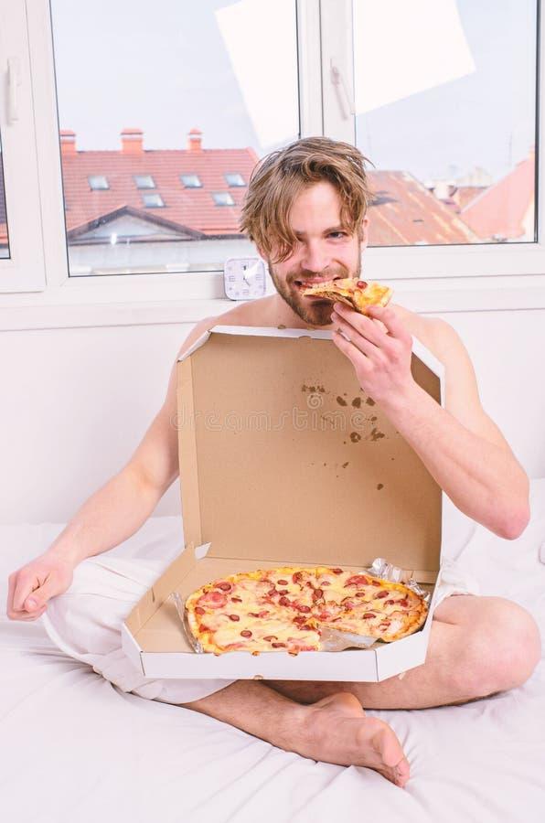 ?ter sk?ggigt stiligt f?r man pizza Mannen ?ter pizzafrukostgrabben som den nakna dolda pizzaasken sitter s?ngsovrumerbjudande, d royaltyfri fotografi