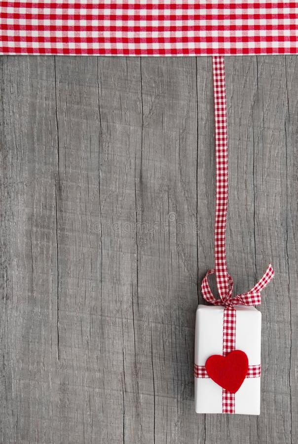 Teraźniejszość na drewnianym tle dla talonu lub alegat z czerwonym sercem obrazy stock