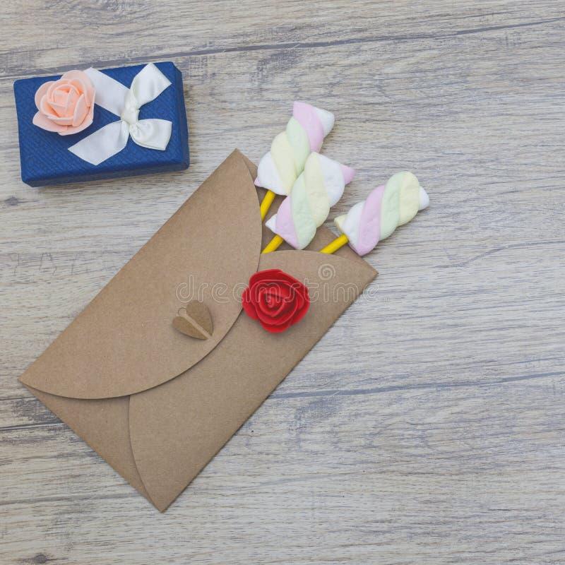 Teraźniejszość, niespodzianka, miłość pojęcia Marshmallow cukierki w kopercie z błękitnym prezenta pudełkiem obrazy royalty free