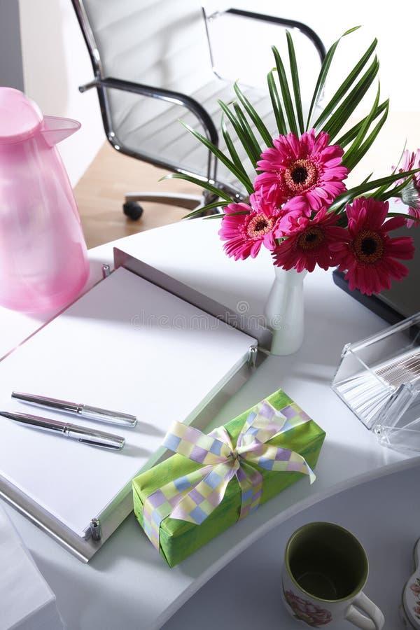 Teraźniejszości i kwiatu waza na biuro stole zdjęcie royalty free