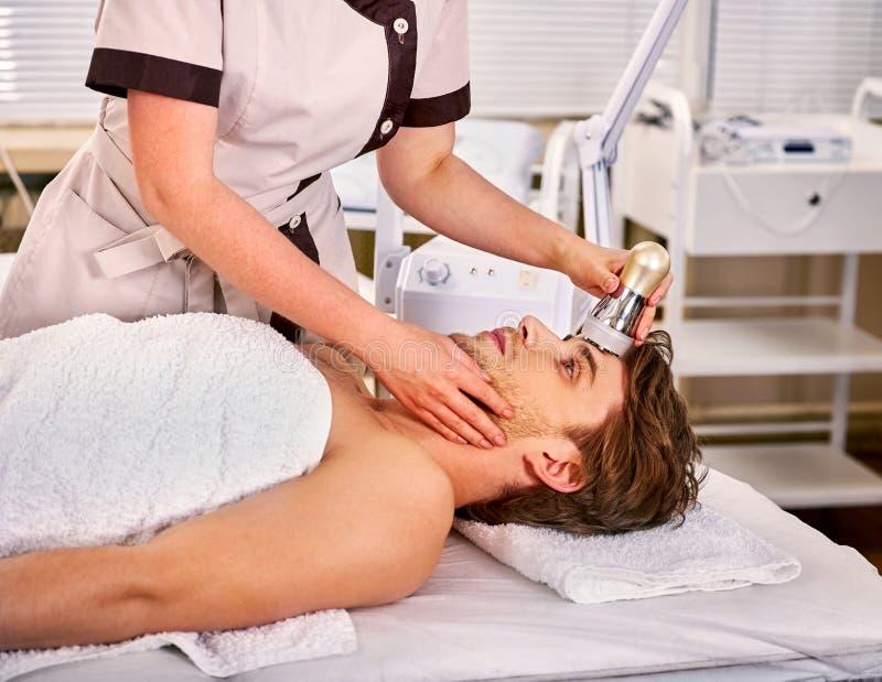 Terapêutica de ultrassons para aperto da pele masculina no salão de beleza foto de stock