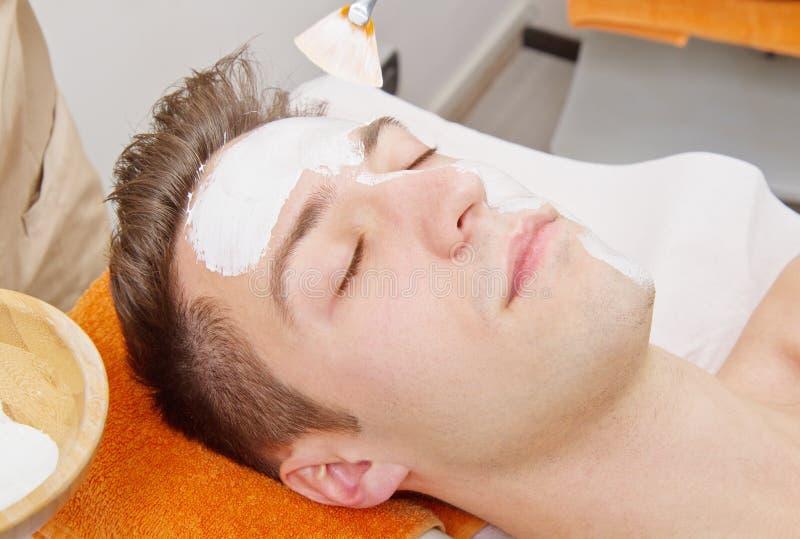 Terapeut som applicerar en framsidamaskering till en härlig ung man i en brunnsort royaltyfri bild