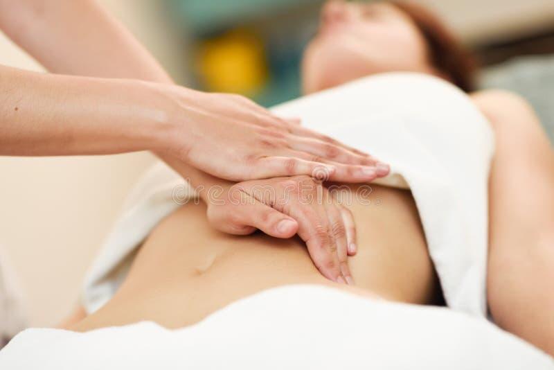 Terapeut som applicerar tryck p? buken Händer som masserar kvinnamagen royaltyfri bild