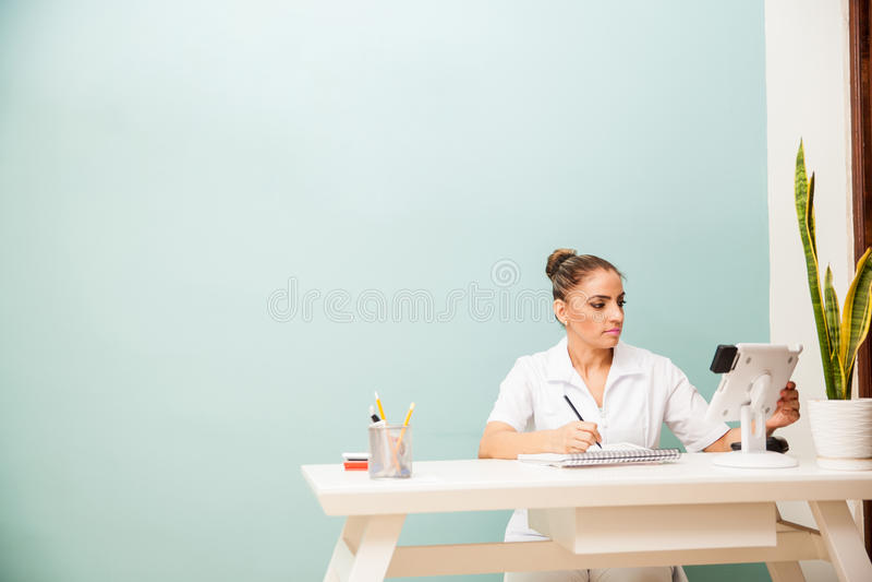Terapeut som arbetar på ett främre skrivbord för brunnsort royaltyfri bild