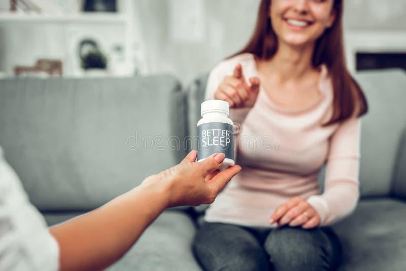 Terapeut som erbjuder några bra sömnpiller till hennes tillfredsställda klient arkivfoto