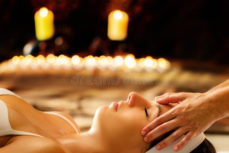 Terapeut som gör den head massagen på kvinna på levande ljus arkivbild