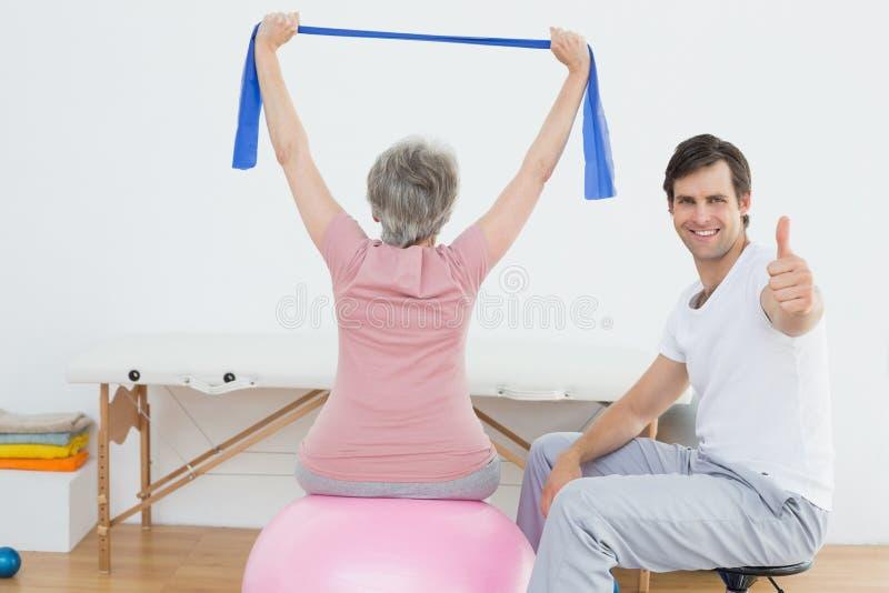 Terapeut som gör en gest upp tummar vid kvinnan på yogaboll arkivfoto